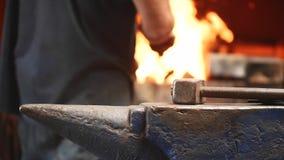O martelo no batente e nas mãos do trabalhador no fundo pôs a madeira na fornalha com fogo filme