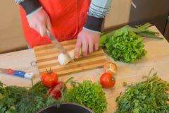 O ` masculino s entrega o cozimento da refeição saudável na cozinha, atrás dos legumes frescos Alimento saudável Imagem colhida d Fotos de Stock