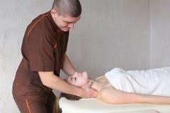 O massagista do indivíduo com mãos fortes amassa o pescoço da moça, que se encontram Fotos de Stock