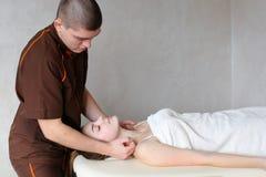 O massagista do indivíduo com mãos fortes amassa o pescoço da moça, que se encontram Fotografia de Stock