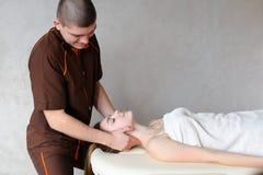 O massagista do indivíduo com mãos fortes amassa o pescoço da moça, que se encontram Fotos de Stock Royalty Free