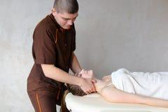 O massagista do indivíduo com mãos fortes amassa o pescoço da moça, que se encontram Foto de Stock Royalty Free