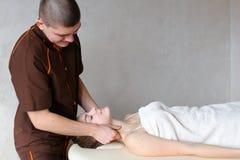 O massagista do indivíduo com mãos fortes amassa o pescoço da moça, que se encontram Imagem de Stock