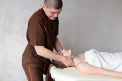 O massagista do indivíduo com mãos fortes amassa o pescoço da moça, que se encontram Imagens de Stock