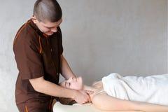 O massagista do indivíduo com mãos fortes amassa o pescoço da moça, que se encontram Fotografia de Stock Royalty Free
