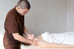 O massagista do indivíduo com mãos fortes amassa o pescoço da moça, que se encontram Foto de Stock