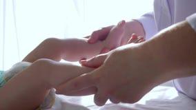 O massagista faz exercícios da ginástica com close-up pequeno da criança, primeira infância saudável video estoque