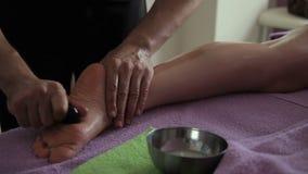 O massagista faz a massagem do pé com as pedras quentes no centro dos termas vídeos de arquivo