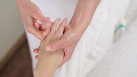 O massagista faz uma massagem da mão e dos dedos de uma mulher video estoque