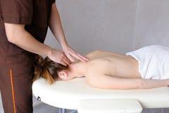O massagista masculino com mãos fortes amassa o pescoço da jovem mulher que li Imagem de Stock
