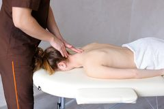 O massagista masculino com mãos fortes amassa o pescoço da jovem mulher que li Foto de Stock Royalty Free