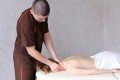 O massagista masculino com mãos fortes amassa o pescoço da jovem mulher que li Imagens de Stock Royalty Free