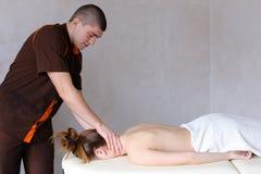 O massagista masculino com mãos fortes amassa o pescoço da jovem mulher que li Fotos de Stock Royalty Free