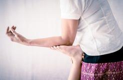 O massagista tailandês está fazendo massagens os pés da mulher usando o cotovelo foto de stock royalty free