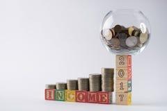 O mealheiro ajustou-se nos blocos número de madeira 2017 com as moedas douradas no frasco do dinheiro Foto de Stock Royalty Free