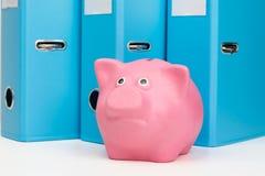 O mealheiro cor-de-rosa com dinheiro está na tabela contra os originais de fundo Fotografia de Stock