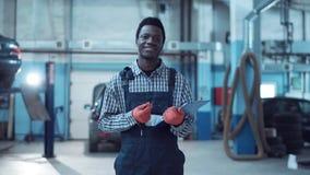 O mecânico africano de sorriso que escreve para fora um trabalho cobre Imagens de Stock
