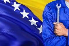 O mecânico bosniano no uniforme azul está mantendo a chave contra a ondulação do fundo da bandeira de Bósnia - de Herzegovina Téc fotografia de stock