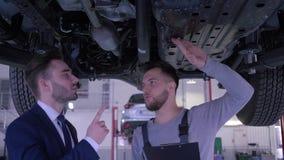 O mecânico com inspeçãos do livro de serviço condiciona o automóvel no elevador hidráulico e na conversa com o cliente no serviço vídeos de arquivo