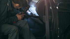 O mecânico com a lâmpada está verificando dentro do carro no serviço do automóvel da garagem, fim acima filme