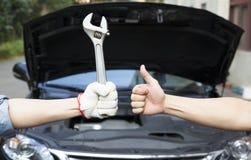 o mecânico com polegares levanta e utiliza ferramentas Imagens de Stock Royalty Free