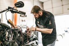 O mecânico da motocicleta que repara a eletrônica ostenta a bicicleta preta Imagem de Stock Royalty Free