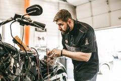 O mecânico da motocicleta que repara a eletrônica ostenta a bicicleta preta Imagem de Stock