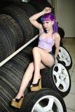 O mecânico de automóvel bonito da menina do moderno trabalha com os pneus nas rodas Fotografia de Stock Royalty Free