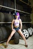 O mecânico de automóvel bonito da menina do moderno trabalha com os pneus nas rodas Foto de Stock