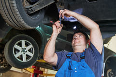 O mecânico de automóvel verifica a suspensão do carro na estação do serviço Fotos de Stock Royalty Free