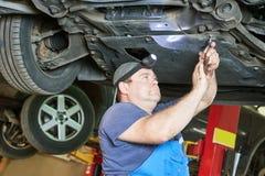 O mecânico de automóvel verifica a suspensão do carro na estação do serviço Imagem de Stock Royalty Free