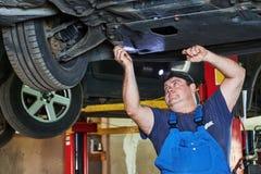 O mecânico de automóvel verifica a suspensão do carro na estação do serviço Imagens de Stock