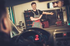 O mecânico de carro dá boas-vindas ao cliente novo a seu serviço de reparação de automóveis Imagem de Stock Royalty Free