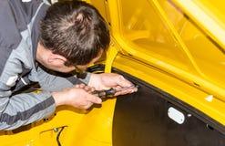O mecânico de carro parafusa as peças do carro junto outra vez após a restauração - oficina do reparo de Serie fotografia de stock royalty free