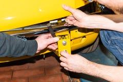 O mecânico de carro parafusa as peças do carro junto outra vez após a restauração - oficina do reparo de Serie fotos de stock royalty free