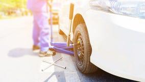 O mec?nico de carro que substitui pneus lisos na estrada Os jaques hidr?ulicos azuis do assoalho do carro levantam os carros e a  imagens de stock