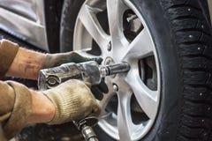 O mecânico de carro substitui as rodas de carro do automóvel levantado pela chave pneumática na estação da garagem da loja do ser Fotos de Stock