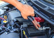 O mecânico de carro usa cabos de ligação em ponte da bateria para carregar um batte inoperante Imagens de Stock