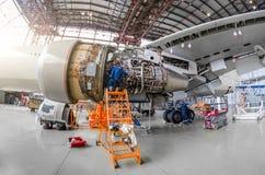 O mecânico do especialista repara a manutenção de um grande motor de um avião de passageiro em um hangar Vista do motor sem capot imagens de stock royalty free