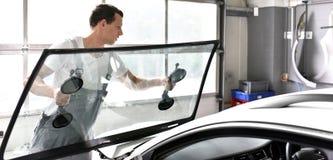 O mecânico em uma garagem substitui o para-brisa defeituoso de um carro imagens de stock