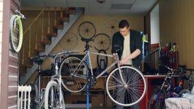 O mecânico experiente na roupa ocasional está verificando o guiador e a roda dianteira da bicicleta então que ajustam e que fixam vídeos de arquivo