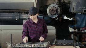 O mecânico fêmea profissional executa o trabalho do reparo do carro no auto serviço video estoque