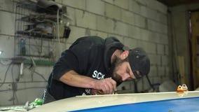 O mecânico farpado adulto do homem concentra a pintura com o aerógrafo na capa do carro video estoque