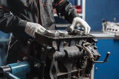 O mecânico instala um pistão novo Desmonte o veículo do bloco de motor Reparo do capital do motor Dezesseis válvulas e quatro fotografia de stock