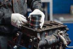O mecânico instala um pistão novo Desmonte o veículo do bloco de motor Reparo do capital do motor Dezesseis válvulas e quatro foto de stock