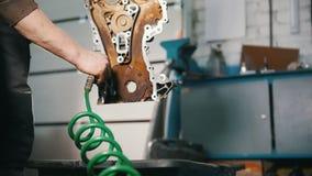 O mecânico limpa as peças de motor, secando com o fluxo de ar, serviço do carro filme