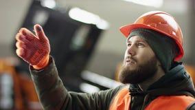 O mecânico profissional de sucesso em retrato faz gestos incríveis e sorrisos segurando uma chave enorme nas mãos Homem barbudo video estoque