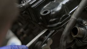 O mecânico que tenta desmonta o motor do velomotor usando a chave de fenda vídeos de arquivo