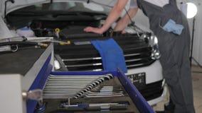 O mecânico que trabalha na oficina, ferramenta profissional nas mãos mechanician, serviço do carro, especialista novo repara os c vídeos de arquivo