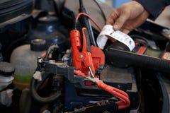 O mecânico que usa o impulsionador cabografa à partida um motor de automóveis fotografia de stock